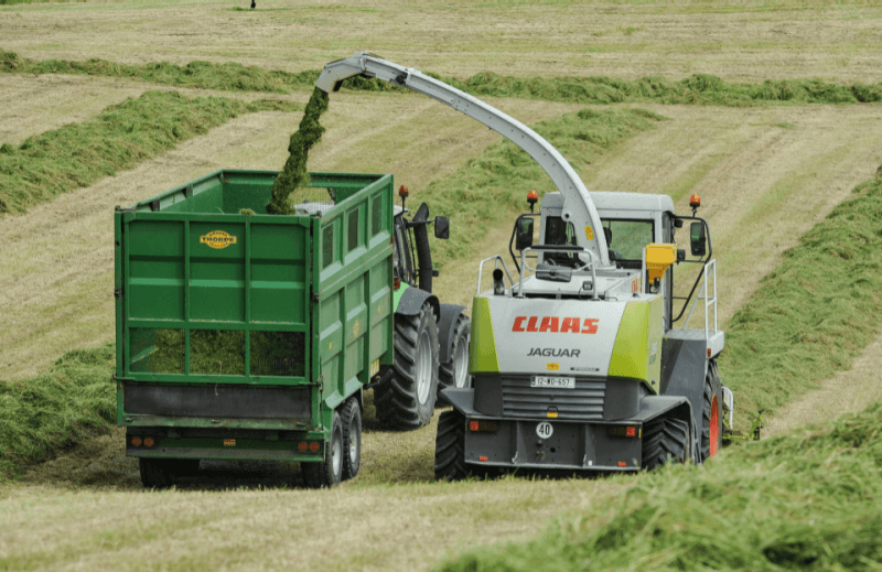combine filling a trailer while harvesting
